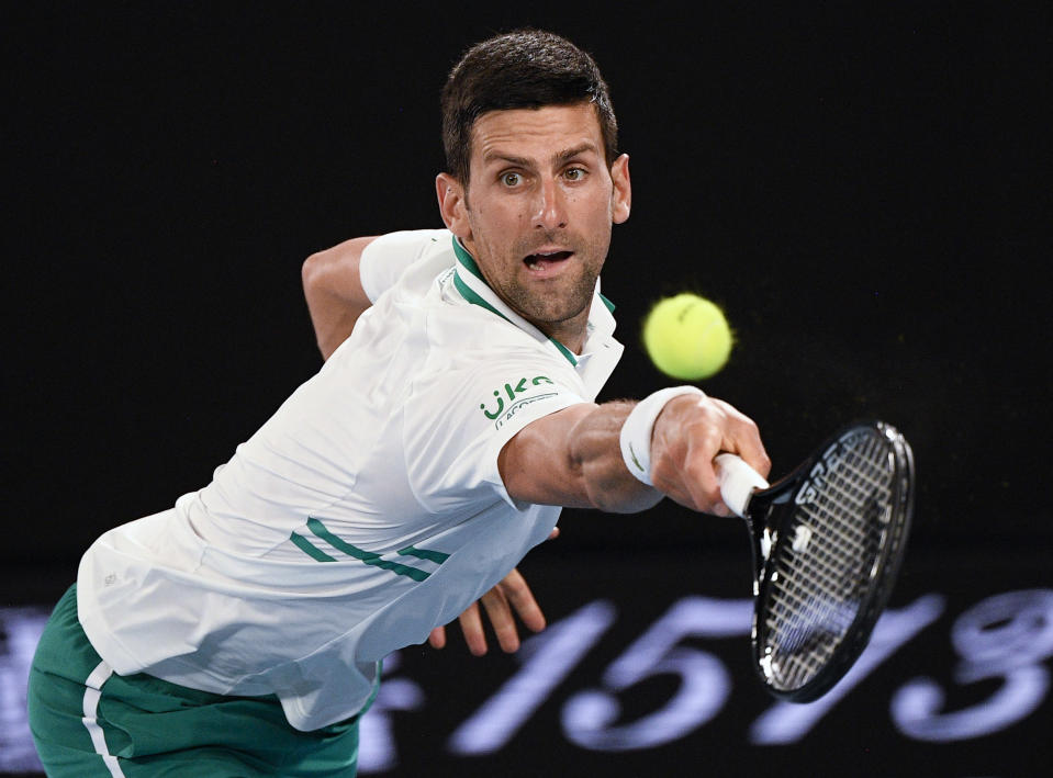 Serbia's Novak Djokovic hits a backhand return to Russia's Aslan Karatsev during their semifinal match at the Australian Open tennis championship in Melbourne, Australia, Thursday, Feb. 18, 2021.(AP Photo/Andy Brownbill)