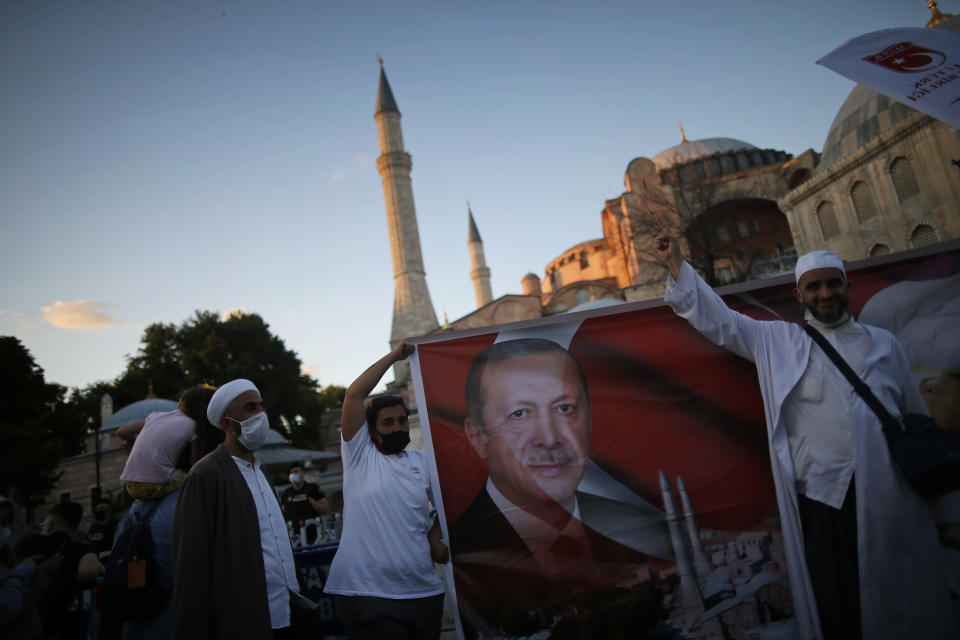 People holding a banner with the image of Turkey's President Recep Tayyip Erdogan', celebrate, outside the Byzantine-era Hagia Sophia, one of Istanbul's main tourist attractions in the historic Sultanahmet district of Istanbul, following Turkey's Council of State's decision, Friday, July 10, 2020.Turkey's highest administrative court issued a ruling Friday that paves the way for the government to convert Hagia Sophia - a former cathedral-turned-mosque that now serves as a museum - back into a Muslim house of worship. The Council of State threw its weight behind a petition brought by a religious group and annulled a 1934 cabinet decision that changed the 6th century building into a museum.(AP Photo/Emrah Gurel)