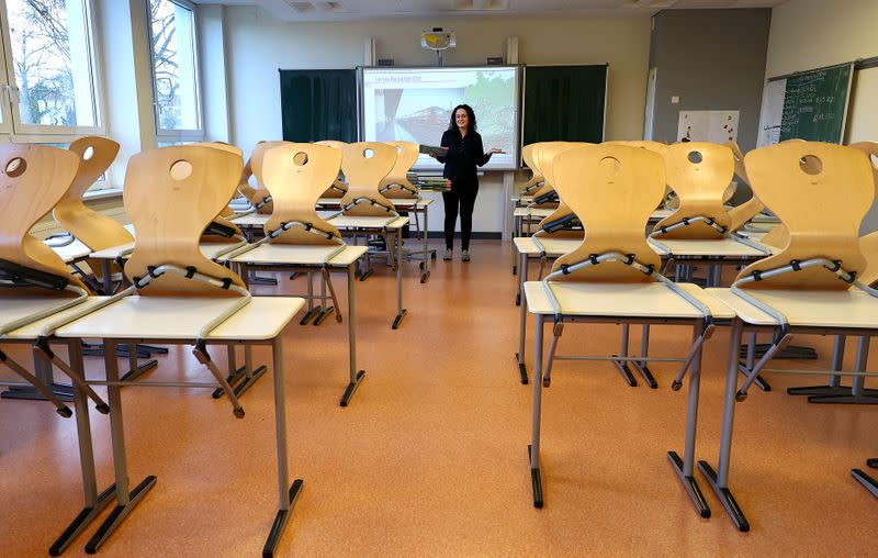 FILE PHOTO: Geography teacher Dinar Pamukci stands in front of the multimedia board at Hesse's largest high school, Karl-Rehbein-Schule, in Hanau, after authorities decided to close schools in most of Germany's federal states due to the coronavirus disease