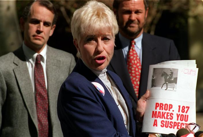 Barbara Coe displays literature distributed by an anti-Proposition 187 group in 1994