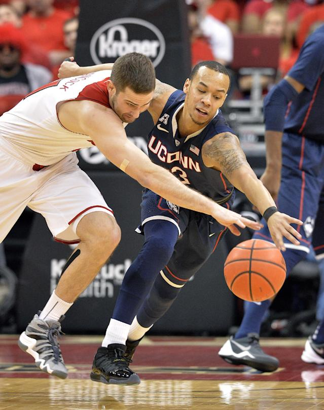 Louisville's Luke Hancock, left, battles Connecticut's Shabazz Napier for a loose ball during the first half of an NCAA college basketball game, Saturday, March 8, 2014, in Louisville, Ky. (AP Photo/Timothy D. Easley)