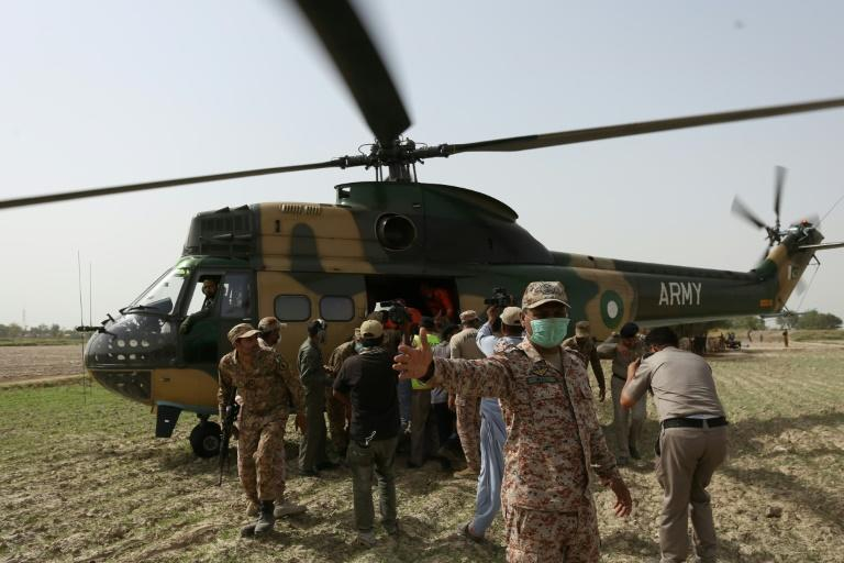Security personnel carry an injured passenger to an army helicopter at the site of the deadlly train accident