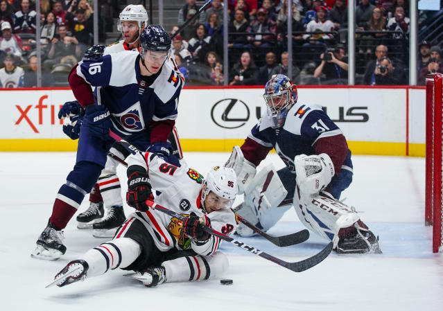 Chicago Blackhawks right wing Dylan Sikura (95) slides on the ice to control the puck against Colorado Avalanche defenseman Nikita Zadorov (16) and Philipp Grubauer (31) during the first period of an NHL hockey game, Saturday, March 23, 2019 in Denver. (AP Photo/Jack Dempsey)