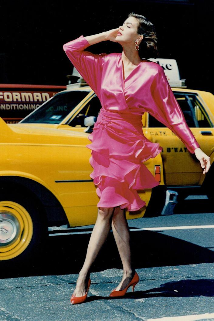 <p>A model wears a fuchsia dress and jeweled earrings out on the street. </p>