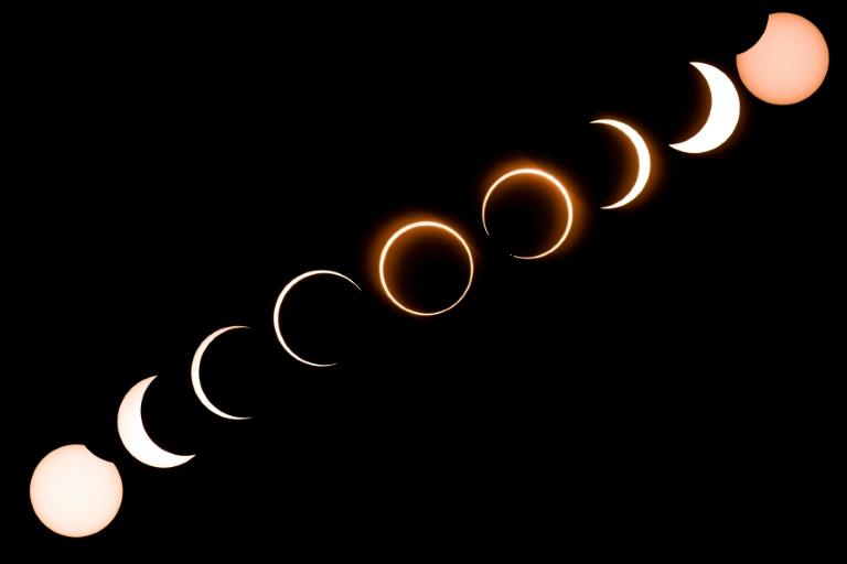 """This composite image shows the moon moving in front of the sun in a rare """"ring of fire"""" solar eclipse as seen from Tanjung Piai in Malaysia on December 26, 2019 (AFP Photo/Sadiq ASYRAF)"""