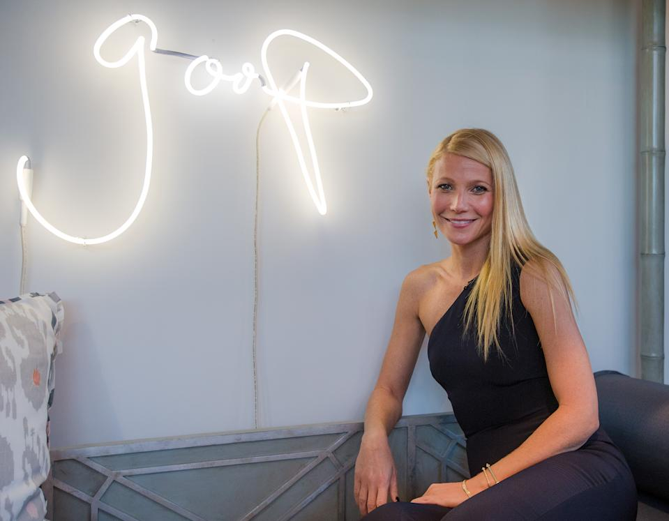 Gwyneth Paltrow poses in front of neon goop sign