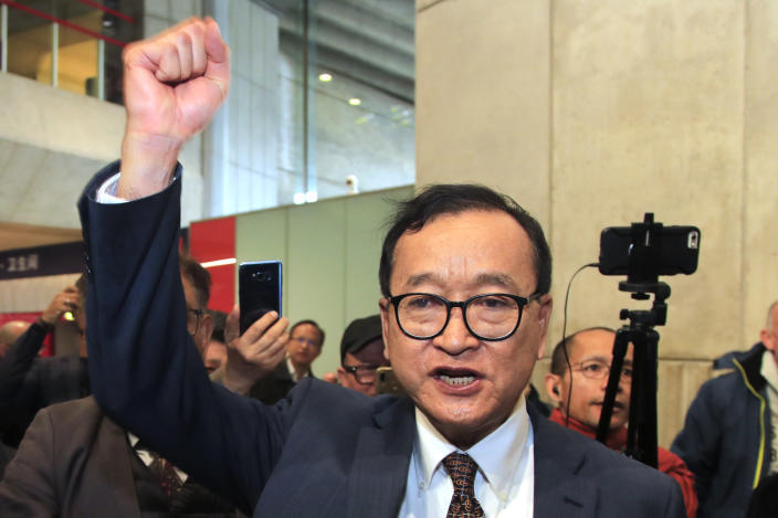 FILE - In this Nov. 7, 2019, file photo, Cambodia's most prominent opposition politician Sam Rainsy clenches his fist as he is attempting to return to Cambodia at Charles de Gaulle airport, north of Paris. Phnom Penh Municipal Court has convicted and sentenced the exiled leader and senior members of the country's banned opposition party to more than 20 years in prison, effectively barring them from ever returning home. The decision taken by the court late Monday, March 1, 2021 was condemned by the head of the Cambodia National Rescue Party , or CNRP, human rights organizations and the United States embassy. The trial was held in absentia as all the party leaders are living abroad. (AP Photo/Michel Euler, File)