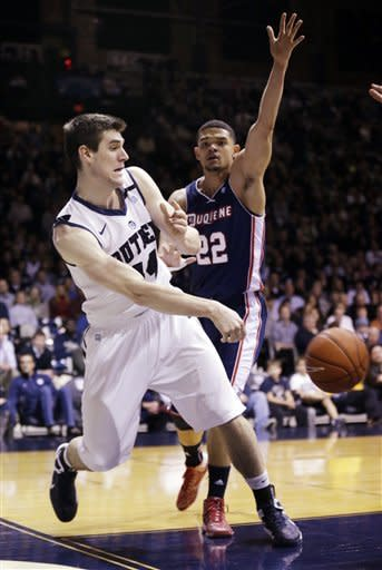 Butler center Andrew Smith, left, makes a pass in front of Duquesne's Kadeem Pantophlet during the first half of an NCAA college basketball game in Indianapolis, Tuesday, Feb. 19, 2013. (AP Photo/Michael Conroy)
