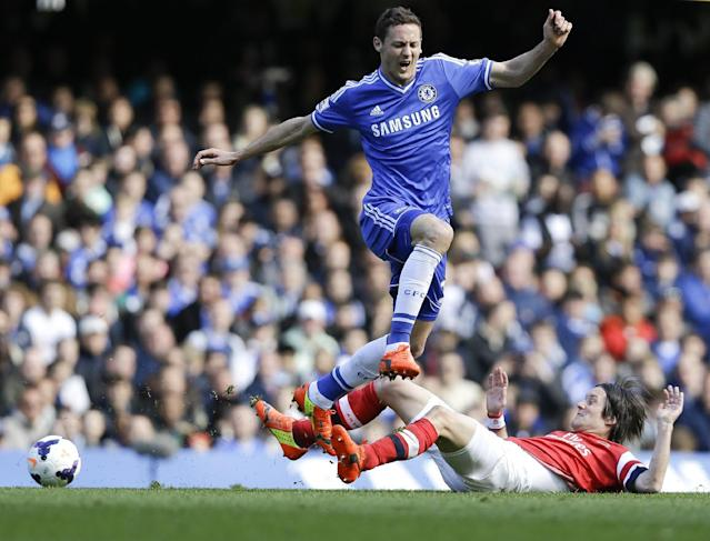 Chelsea's Nemanja Matic leaps over Arsenal's Tomas Rosicky during the English Premier League soccer match between Chelsea and Arsenal at Stamford Bridge stadium in London, Saturday, March 22, 2014. (AP Photo/Kirsty Wigglesworth)