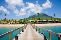"It may be smaller than St. Kitts, but Nevis holds its own. The birthplace of Alexander Hamilton is almost perfectly round, with gentle slopes rising to the peak of its dormant volcano, and the island is known for its historic inns and top-drawer resorts. Set up camp at the <a href=""https://www.cntraveler.com/hotels/saint-kitts-and-nevis/vaughans/four-seasons-resort--nevis?mbid=synd_yahoo_rss"" rel=""nofollow noopener"" target=""_blank"" data-ylk=""slk:Four Seasons Resort Nevis"" class=""link rapid-noclick-resp"">Four Seasons Resort Nevis</a> for easy access to Pinney's Beach, a favorite for both families with kids, and travelers seeking a calm respite. The beach lets you walk for nearly three miles along the island's sheltered west coast, where you can soak in the views of towering palms and the cloud-covered peak of Mount Nevis."