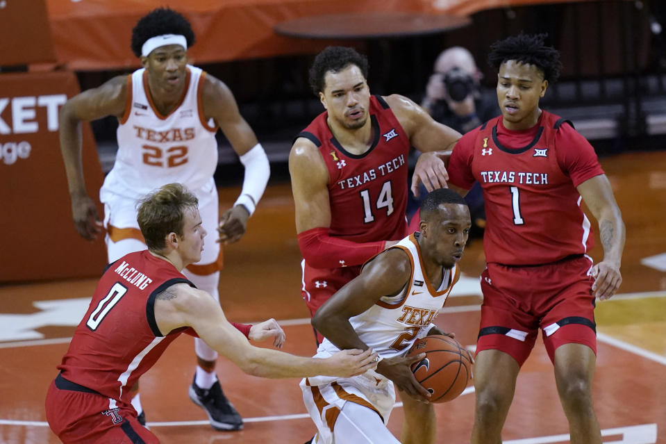 Texas guard Matt Coleman III (2) grabs a rebound as Texas Tech's Mac McClung, Marcus Santos-Silva and Terrence Shannon Jr., from left, defend during the first half of an NCAA college basketball game Wednesday, Jan. 13, 2021, in Austin, Texas. (AP Photo/Eric Gay)