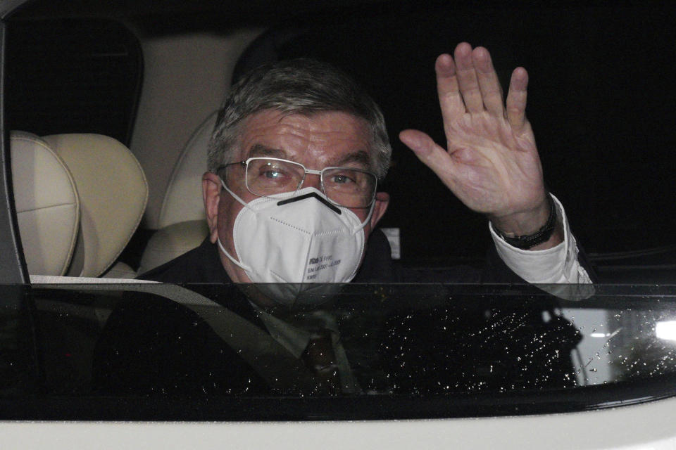 International Olympic Committee (IOC) President Thomas Bach waves from the vehicle to media upon his arrival an accommodation Thursday, July 8, 2021, in Tokyo. Bach arrived on Thursday, July 8, 2021, in Tokyo as Japan Prime Minister Yoshihde Suga was set to declare a state of emergency that is likely to result in a ban on fans from the Tokyo Olympics as coronavirus infections spread across the capital. (AP Photo/Eugene Hoshiko, Pool)
