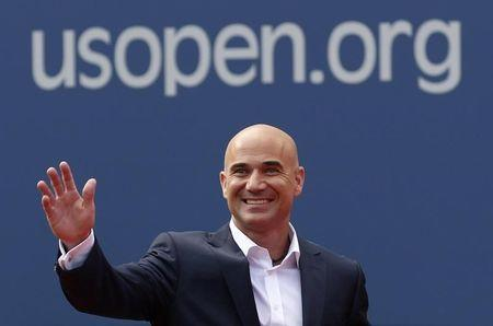 FILE PHOTO: Two-time U.S. Open champion Andre Agassi waves before being inducted into the U.S. Open Court of Champions, which celebrates the legacy of the greatest singles champions in the history of the tournament, in New York September 9, 2012. REUTERS/Kevin Lamarque