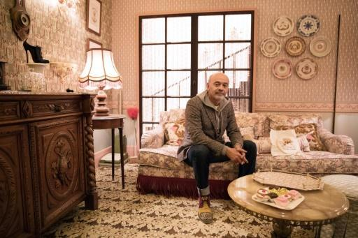 """Louboutin in """"the English granny's sitting room"""" of his new Paris show. A closer look reveals that many of the granny's ornaments are rather risque"""