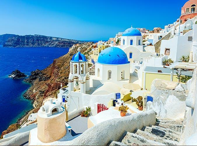 """<p><a href=""""https://www.purewow.com/travel/instagrams-of-santorini"""" rel=""""nofollow noopener"""" target=""""_blank"""" data-ylk=""""slk:Santorini"""" class=""""link rapid-noclick-resp"""">Santorini</a> might be a cliché, but it's a cliché for good reason. <a href=""""https://www.purewow.com/travel/best-european-islands"""" rel=""""nofollow noopener"""" target=""""_blank"""" data-ylk=""""slk:The island's"""" class=""""link rapid-noclick-resp"""">The island's</a> most famous village is Oia, where narrow, hilly streets lined with whitewashed houses and pink bougainvillea lead to the cobalt Aegean Sea.</p>"""