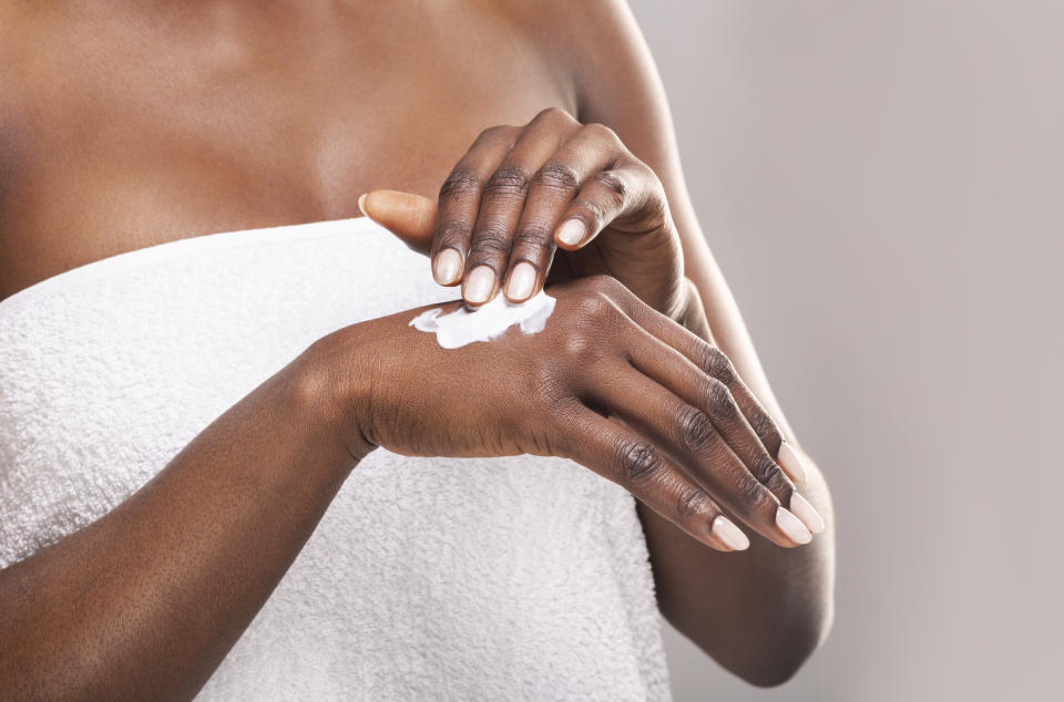 African girl in white bath towel applying body milk on her hand, free space