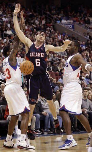 Atlanta Hawks' Kirk Hinrich, center, cannot get a shot off as Philadelphia 76ers' Lou Williams, left, and Jodie Meeks defend in the first half of an NBA basketball game on Saturday, March 31, 2012, in Philadelphia. (AP Photo/Matt Slocum)