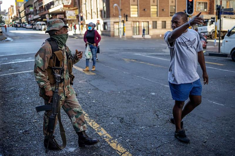 A soldier talks to a man in the street