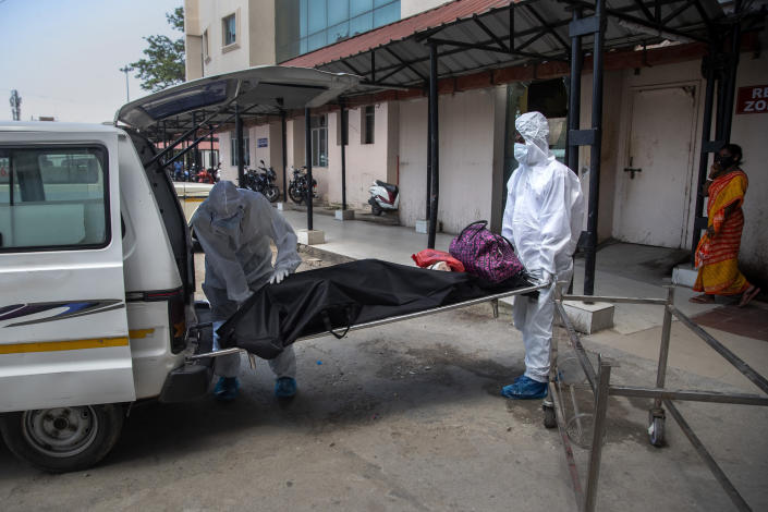 Health workers in protective suits shift the body of a COVID-19 victim at a government hospital in Gauhati, India, Monday, May 24, 2021. India crossed another grim milestone Monday of more than 300,000 people lost to the coronavirus as a devastating surge of infections appeared to be easing in big cities but was swamping the poorer countryside. (AP Photo/Anupam Nath)