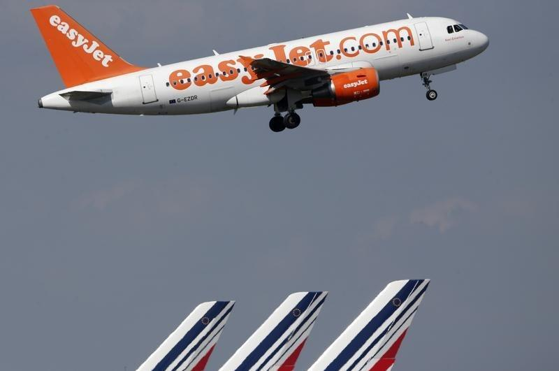 An easyJet aircraft takes-off past Air France plane tails at the Charles-de-Gaulle airport