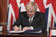 Britain's Prime Minister Boris Johnson signs the EU-UK Trade and Cooperation Agreement at 10 Downing Street, London Wednesday Dec. 30, 2020. The U.K. left the EU almost a year ago, but remained within the bloc's economic embrace during a transition period that ends at midnight Brussels time —- 11 p.m. in London — on Thursday. European Commission President Ursula von der Leyen and European Council President Charles Michel signed the agreement during a brief ceremony in Brussels on Wednesday morning then the documents were flown by Royal Air Force plane to London for Johnson to add his signature. (Leon Neal/Pool via AP)