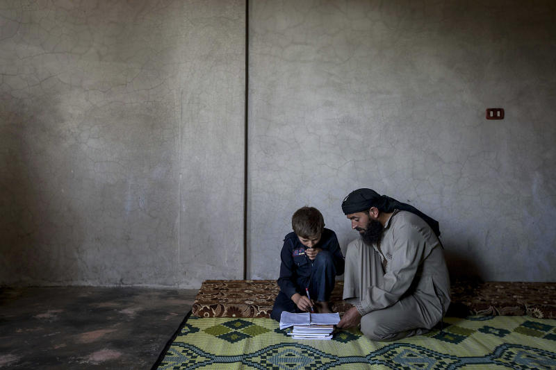 In this Sunday, Sept. 29, 2013 photo, Ahmed al-Fikri helps his 12-year-old son Abdo al-Fikri, with his homework at their family house in Madaya village after school in the Idlib province countryside of Syria. It has been a year since al-Fikri and his siblings were last in school. The area has seen ongoing battles between opposition forces and troops loyal to President Bashar Assad, and like pretty much everything else in Madaya, the school was forced to shut down because of the violence. (AP Photo)