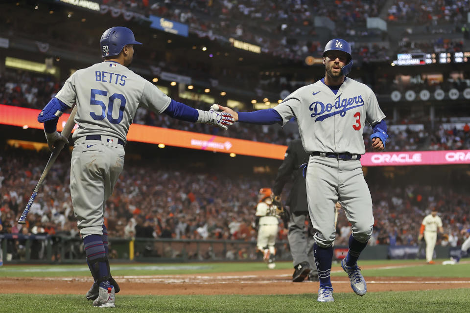 Los Angeles Dodgers' Chris Taylor (3) is congratulated by Mookie Betts (50) after scoring against the San Francisco Giants during the second inning of Game 2 of a baseball National League Division Series Saturday, Oct. 9, 2021, in San Francisco. (AP Photo/John Hefti)
