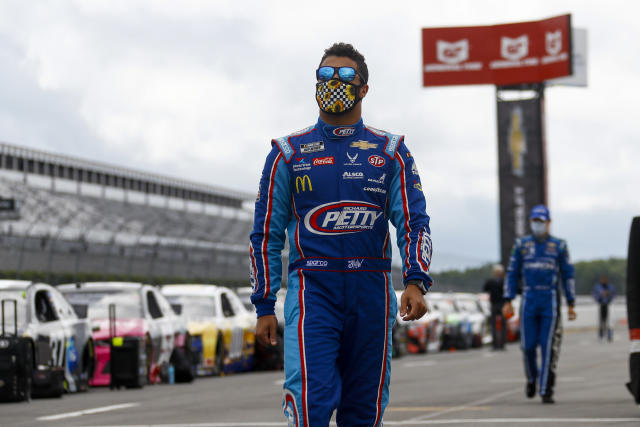 Bubba Wallace walks down pit row down before the start of a NASCAR Cup Series auto race at Pocono Raceway, Saturday, June 27, 2020, in Long Pond, Pa. (AP Photo/Matt Slocum)