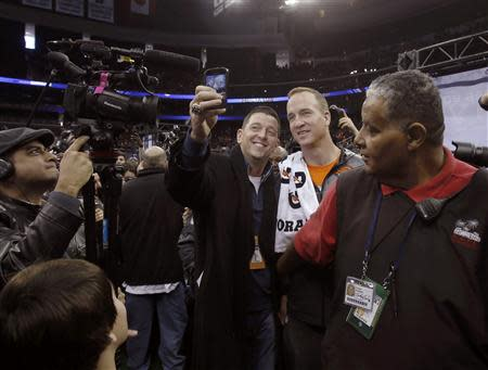 Denver Broncos quarterback Peyton Manning poses for a picture as he departs during Media Day for Super Bowl XLVIII at the Prudential Center in Newark, New Jersey January 28, 2014. REUTERS/Carlo Allegri