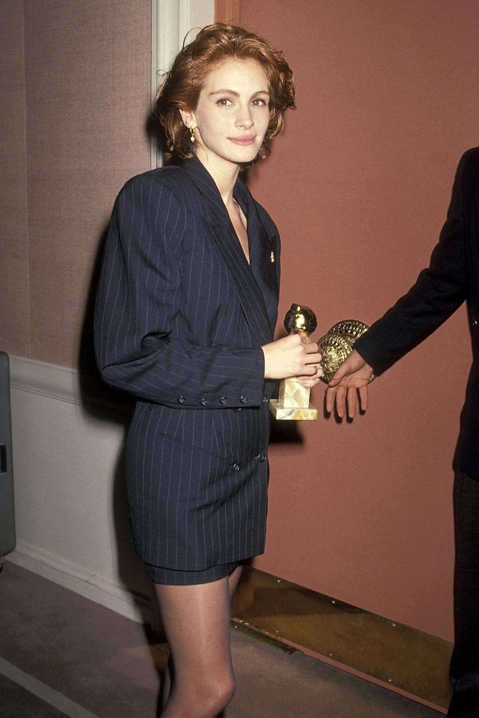 """<strong><h2>1991</h2></strong><br><em>Ahh</em>, the skirt suit. It's no surprise this two-piece trend is making a major comeback when you look at Julia Roberts in this navy blue pinstripe style.<br><br><em>Julia Roberts in a navy blue suit. </em><span class=""""copyright"""">Photo: Ron Galella, Ltd./WireImage.</span>"""