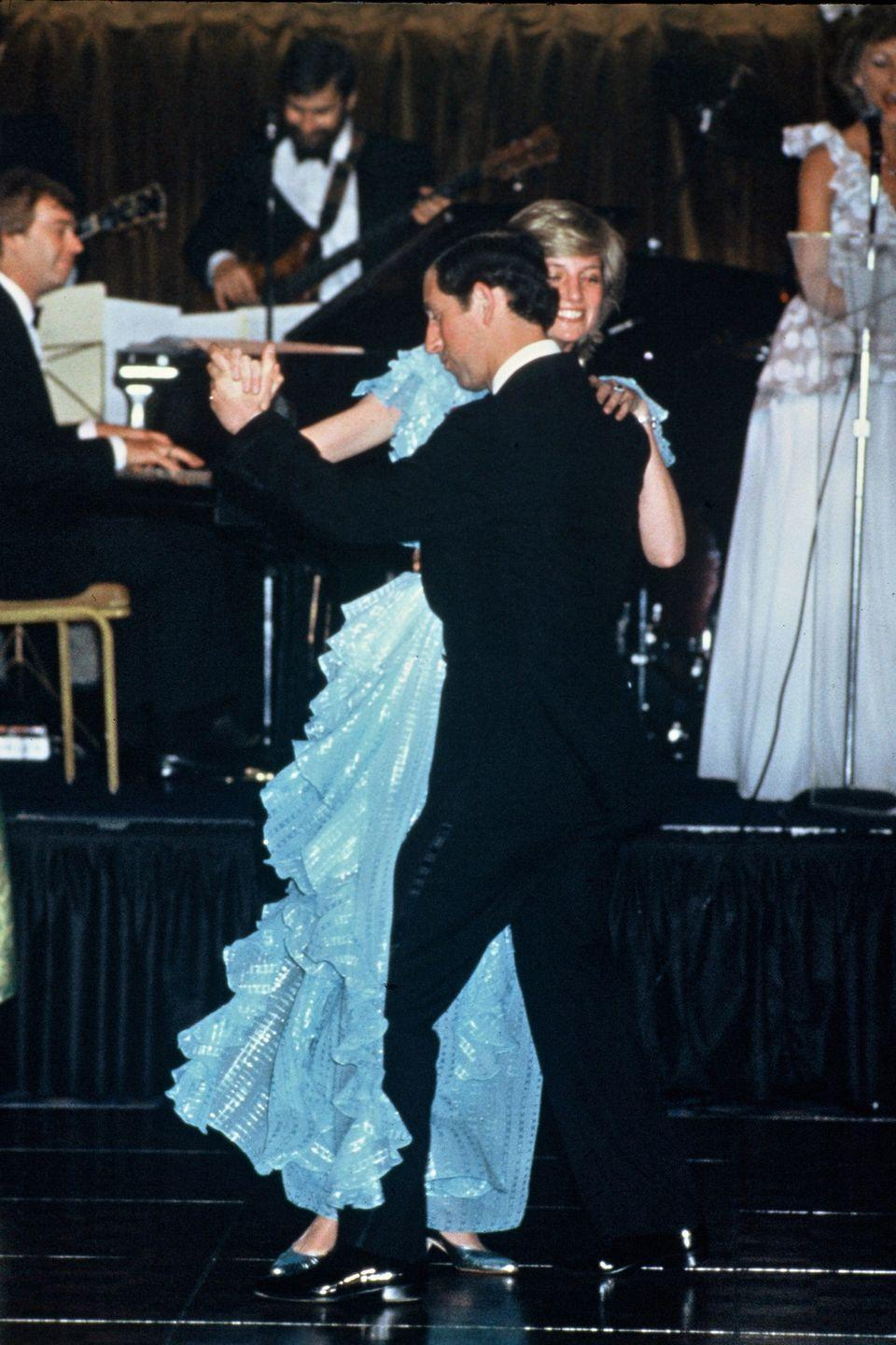 <p>Diana wears a blue, ruffled Bruce Oldfield dress while dancing with the Prince of Wales in Sydney. </p>