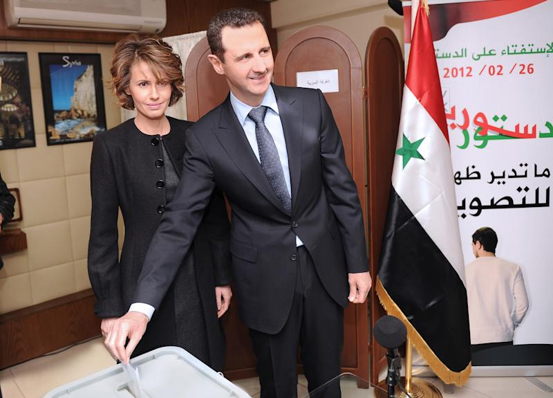 FILE - In this Sunday Feb. 26, 2012 file photo released by the Syrian official news agency SANA, Syrian President Bashar Assad casts his ballot next to his wife Asma at a polling station during a referendum on the new constitution, in Damascus, Syria. As Syria's bloodshed deepens, the country's British-born first lady has become an object of contempt for many, a Marie Antoinette figure who shopped online for fondue sets and 6-inch, crystal-encrusted Christian Louboutin heels while her country burned. The EU has slapped sanctions on Asma Assad, the young, stylish wife who for a decade offered a veneer of respectability to one of the world's most secretive and ruthless dictatorships.(AP Photo/SANA, File)