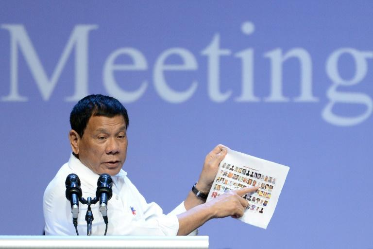 Rodrigo Duterte shows images of allegedly criminal Philippine politicians at a meeting with the Filipino community in Singapore on December 16, 2016