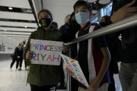 Children from the Mogul family, hold signs for their cousins as they wait for them to arrive on a flight from Charlotte, North Carolina, in the U.S., at Terminal 5 of Heathrow Airport in London, Monday, Aug. 2, 2021. Travelers fully vaccinated against coronavirus from the United States and much of Europe were able to enter Britain without quarantining starting today, a move welcomed by Britain's ailing travel industry. (AP Photo/Matt Dunham)