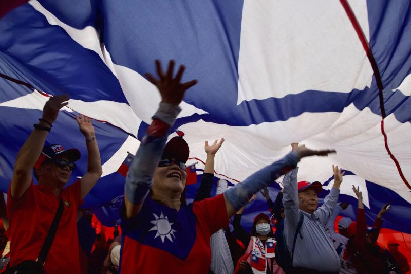 Supporters of Han Kuo-yu, Taiwan's 2020 presidential election candidate of the KMT or Nationalist Party, pass under a giant Taiwanese flag during a campaign rally in southern Taiwan's Kaohsiung city on Friday, Jan 10, 2020. Taiwan will hold its presidential election on Jan. 11, 2020. (AP Photo/Ng Han Guan)