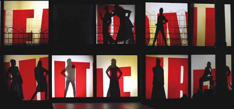 Silhouettes of models behind screens that display the name of French fashion designer Jean-Paul Gaultier as part of his Ready to Wear Fall-Winter 2013-2014 fashion collection, presented, Saturday, March 2, 2013 in Paris. (AP Photo/Jacques Brinon)