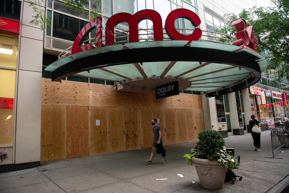 NEW YORK, NEW YORK - SEPTEMBER 24: A man wearing a mask walks past a boarded up an AMC movie theater at 34th Street as the city continues Phase 4 of re-opening following restrictions imposed to slow the spread of coronavirus on September 24, 2020 in New York City.