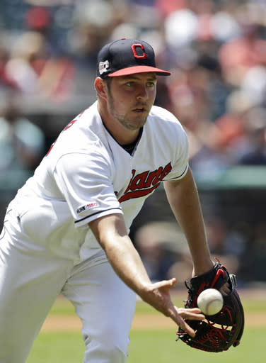 Cleveland Indians starting pitcher Trevor Bauer tosses the ball to first base to get Kansas City Royals' Whit Merrifield out in the fifth inning in a baseball game, Wednesday, June 26, 2019, in Cleveland. (AP Photo/Tony Dejak)