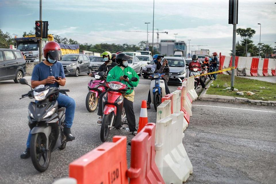 Motorists crowd around the blocked entrance of Persiaran Sungai Buloh as the conditional control movement order kicks in on October 14, 2020. — Picture by Ahmad Zamzahuri