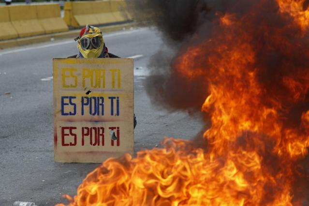 """<p>A demonstrator holds a sign that doubles a shield that reads in Spanish """"It's for you,"""" during a national sit-in against President Nicolas Maduro, in Caracas, Venezuela, Monday, May 15, 2017. (AP Photo/Ariana Cubillos) </p>"""
