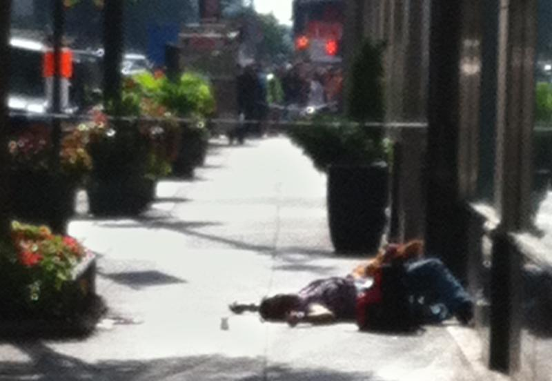 A body lies on the sidewalk near the Empire State Building after a shooting, Friday, Aug. 24, 2012, in New York. At least four people were shot and the gunman was dead, New York City officials said. A witness said the gunman was firing indiscriminately. (AP Photo/Gina Abdy)