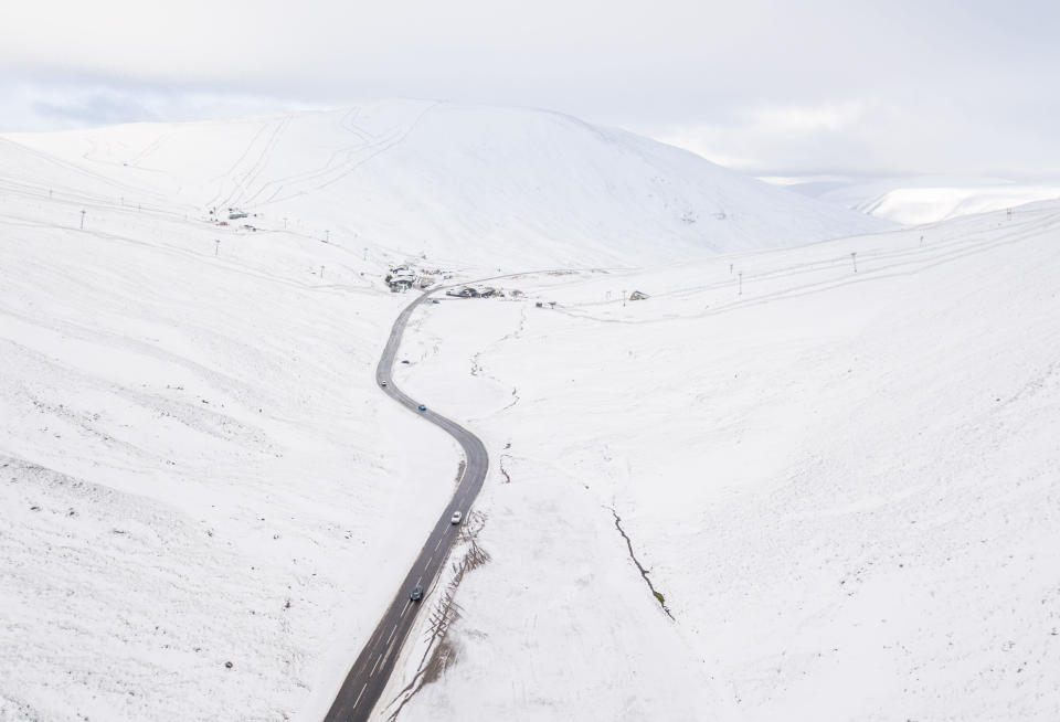 <p>A cleared road winds through snowy hills </p>