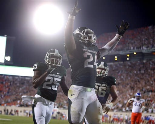 Michigan State's Le'Veon Bell (24) celebrates with teammates Keith Mumphrey (25) and Jack Allen (66) after scoring the game-winning touchdown against Boise State during the fourth quarter of an NCAA college football game, Friday, Aug. 31, 2012, in East Lansing, Mich. At right is Boise State's Ricky Tjong-A-Tjoe (AP Photo/Al Goldis)