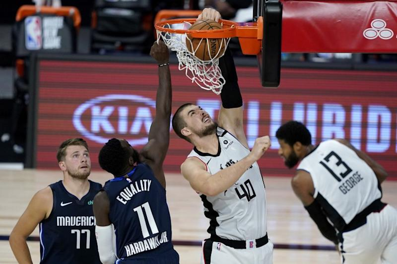 Los Angeles Clippers' Ivica Zubac (40) dinks on Dallas Mavericks' Tim Hardaway Jr. (11) during the first half of an NBA basketball game Thursday, Aug. 6, 2020 in Lake Buena Vista, Fla. Mavericks' Luka Doncic (77) looks on during the play. (AP Photo/Ashley Landis, Pool)