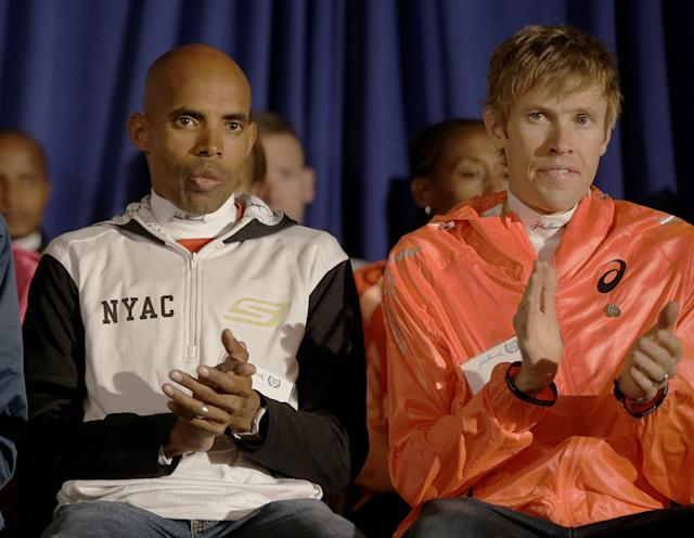 Boston Marathon runners Meb Keflezighi and Ryan Hall applaud during introductions at a media availability of Boston Marathon elite runners at the Copley Plaza Hotel in Boston Friday April 18, 2014. The 118th running of the Boston Marathon is Monday April 21, 2014. (AP Photo/Stephan Savoia)