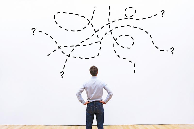 Man with hands on hips looking at complicated diagram on a wall