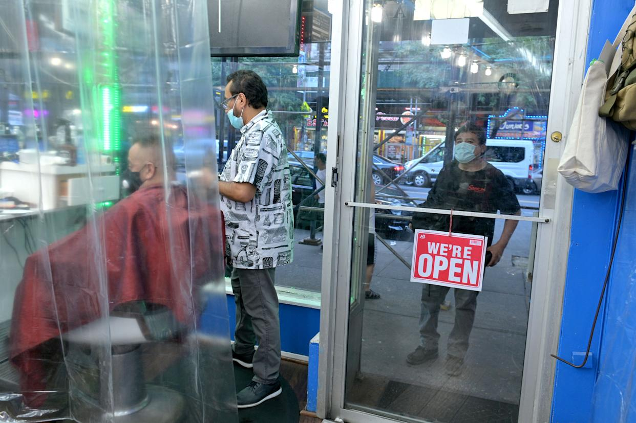 A customer who showed up after closing is turned down at the door by owner Abraham Gaona while he cuts a customer's hair during the second day of the reopening of Abraham's Barber Shop on June 23, 2020 in Washington Heights.