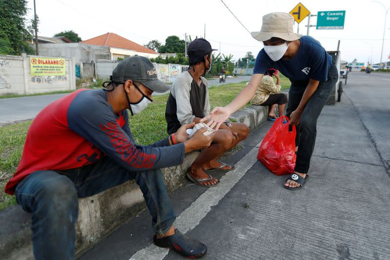 Men get free food from a volunteer, amid the coronavirus disease (COVID-19) outbreak