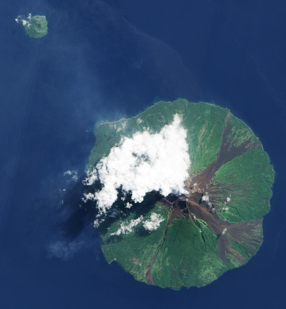 Papua New Guinea's Manam Volcano is pictured as it releases a thin, faint plume, as clouds cluster at the volcano's summit. The volcanic plume appears as a thin, blue-grey veil extending toward the northwest over the Bismarck Sea. Photo credit: Nasa