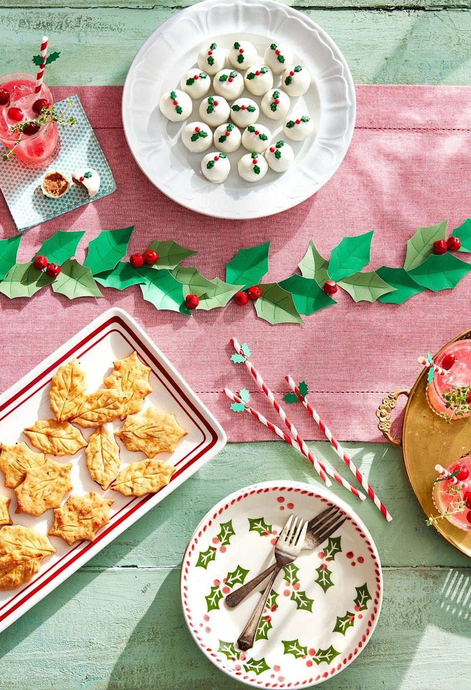 """<p>To express your creativity, make your own leaf garland out of green craft paper. Add red jingle bells to finish the festive look.</p><p><a class=""""link rapid-noclick-resp"""" href=""""https://go.redirectingat.com?id=74968X1596630&url=https%3A%2F%2Fwww.michaels.com%2Fcreatology-construction-paper-9-in-x-12-in-yellow%2F10625533.html&sref=https%3A%2F%2Fwww.goodhousekeeping.com%2Fholidays%2Fchristmas-ideas%2Fhow-to%2Fg2196%2Fchristmas-table-settings%2F"""" rel=""""nofollow noopener"""" target=""""_blank"""" data-ylk=""""slk:SHOP GREEN CRAFT PAPER"""">SHOP GREEN CRAFT PAPER</a></p>"""